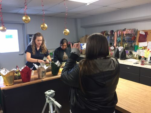 Katlyn capturing students putting together bouquets in the shop.